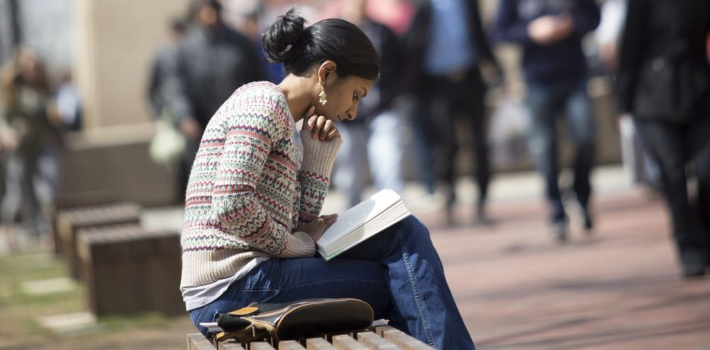 Person sitting on a bench reading a book