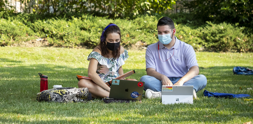 Two students wearing masks sitting on grass