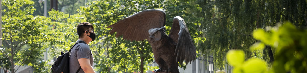 Student wearing a mask walking by Owl statue.
